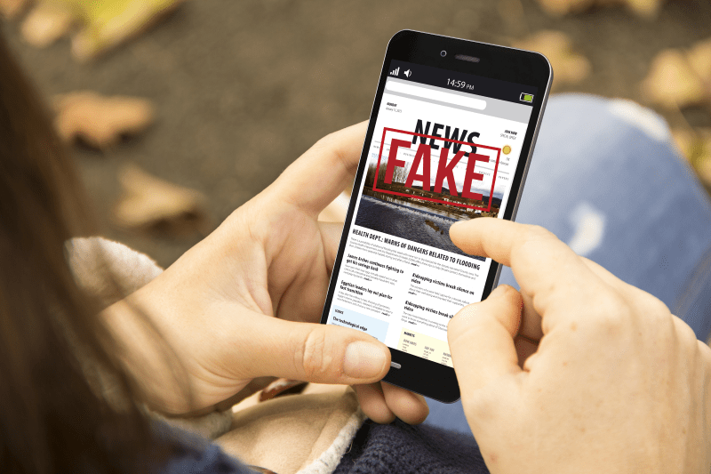 Man holding mobile phone with Fake News headline