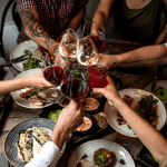 people eating at table clinking glasses