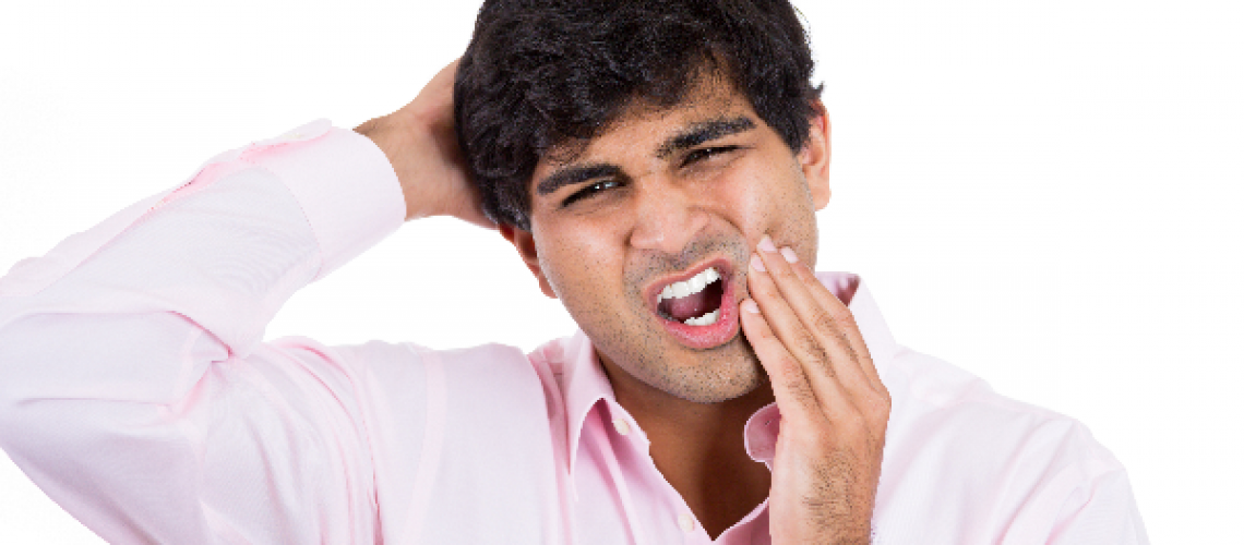Man holding head and chin indicating headache and tootache